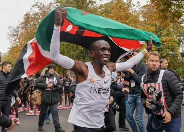 Free for editorial use and archive. Eliud Kipchoge celebrates with a Kenyan flag after crossing finish line to break the historic two hour barrier for a marathon. The INEOS 1:59 Challenge, Vienna, Austria. 12 October 2019. Photo: Jed Leicester for The INEOS 1:59 Challenge